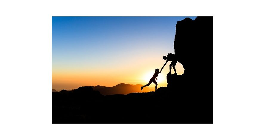 Teamwork couple helping hand trust help silhouette in mountains sunset. Team of climbers man and woman hikers help each other on top of mountain climbing together beautiful sunset landscape on Gran Canaria